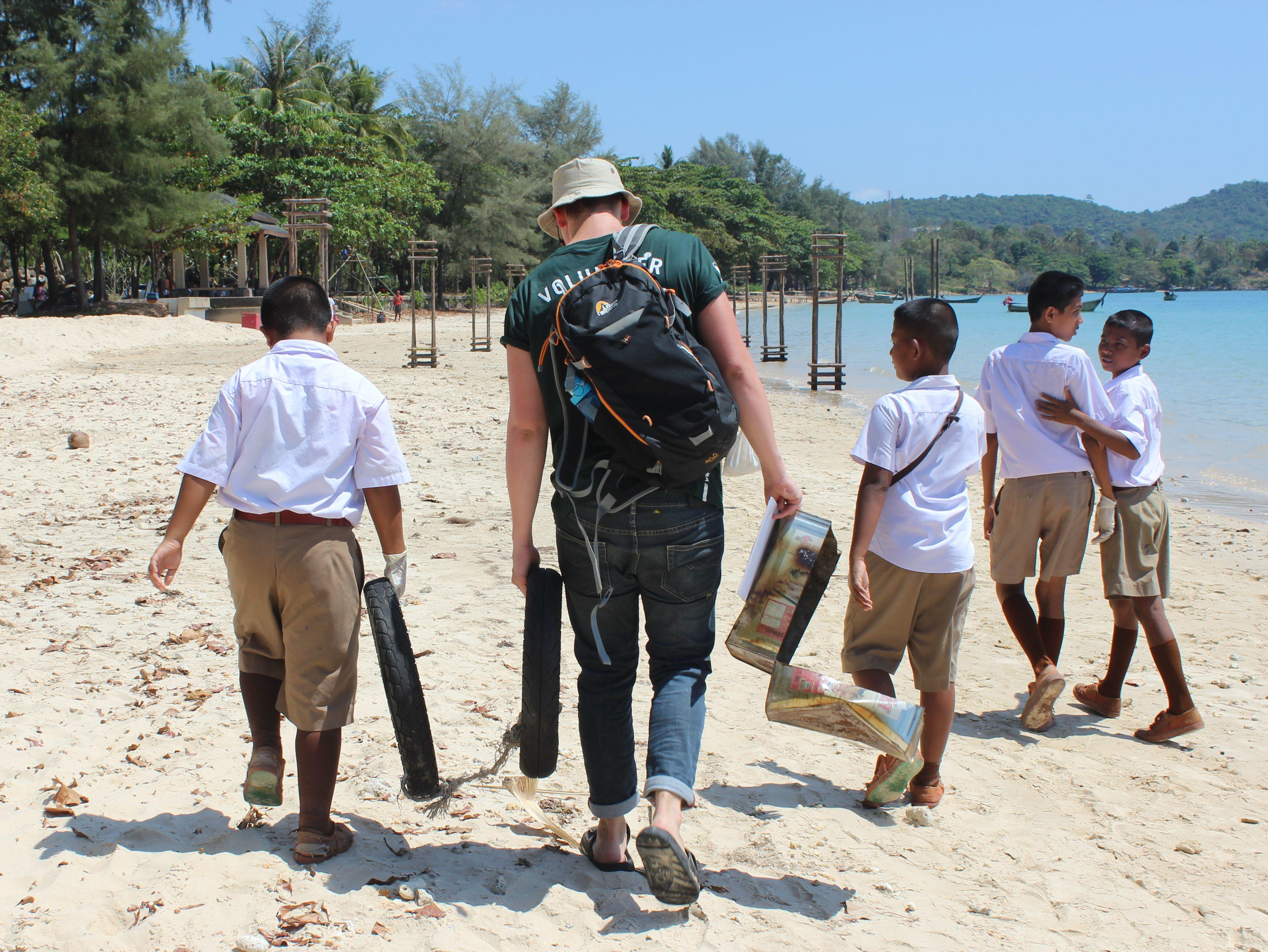 Projects Abroad volunteer is pictured with a group of local children conducting a beach clean up operation as part of his marine conservation work in Thailand.
